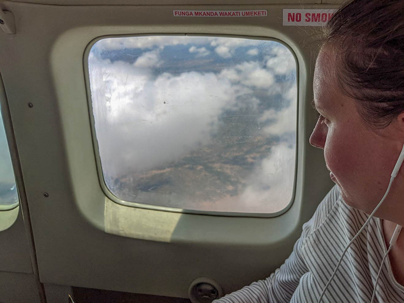 Girl sitting next to window on a small plane over Kenya