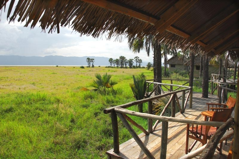 A safari lodge in Africa with chairs on a balcony overlooking the plains