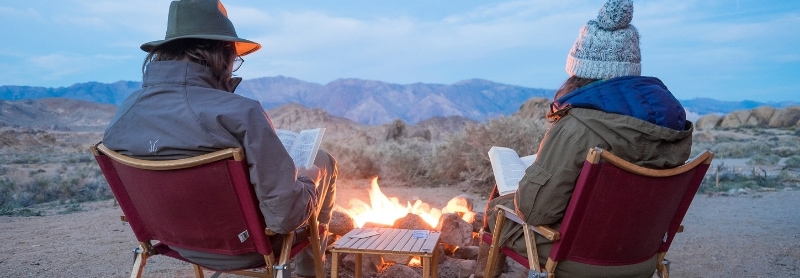 A couple reading safari books in front of a campfire overlooking the mountains